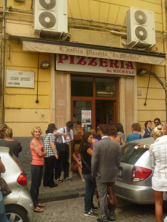 Pizzeria-hole in the wall with people waiting...good sign!