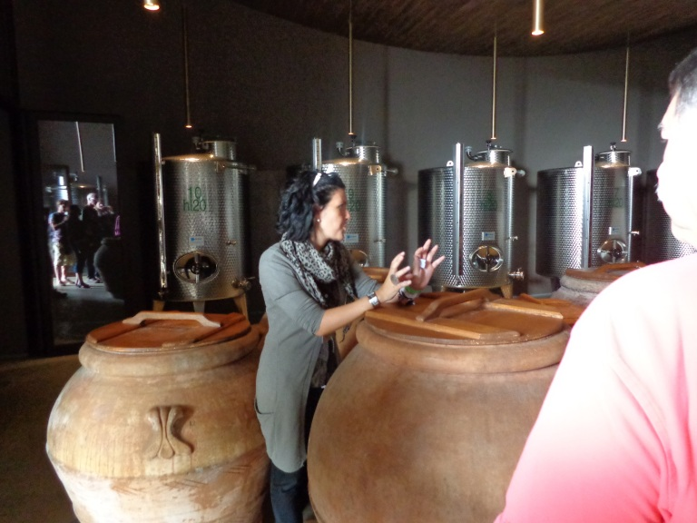 My tour guide explains Olive oil as she leans on a container of some