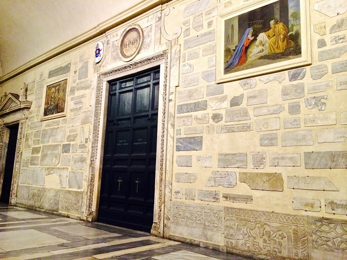 Large entry doors surrounded by ancient sarcophogus marble sections