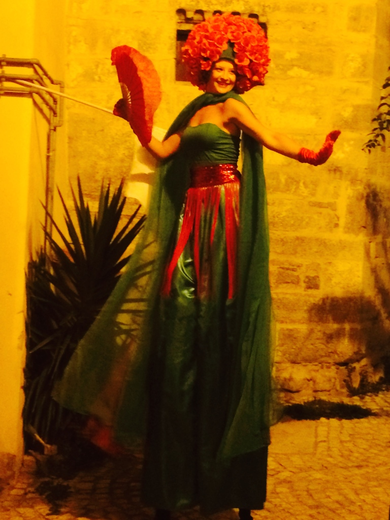 Very tall dancer walking the medieval streets at night